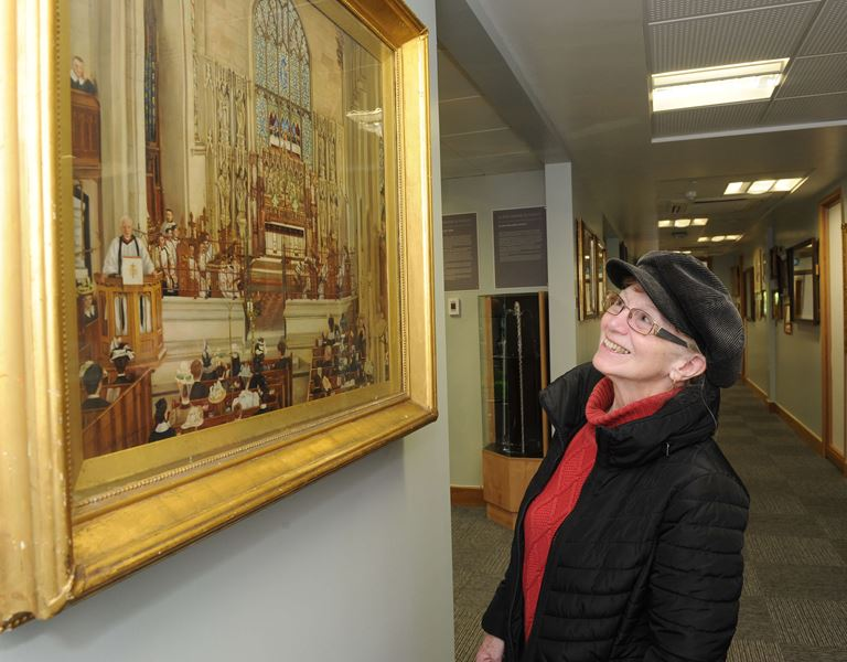 Woman in Art Gallery looking at painting of the inside of Wordsley Church