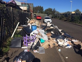 a heap of rubbish dumped at the side of the road and pavement
