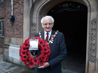 A photo of the Mayor with a poppy wreath in front of the Clock Tower in Dudley